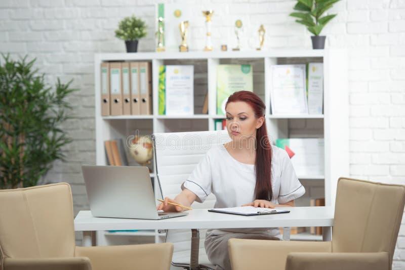 Säker kvinnadoktor som sitter på tabellen i hennes kontor och ler på kameran vart begreppshanden har den sena pillen f?r sjukv?rd arkivfoto