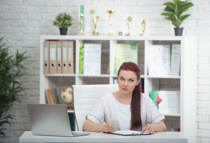 Säker kvinnadoktor som sitter på tabellen i hennes kontor och ler på kameran vart begreppshanden har den sena pillen f?r sjukv?rd arkivbild