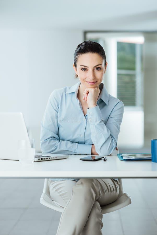 Säker kvinnlig chef på att posera för skrivbord arkivbild