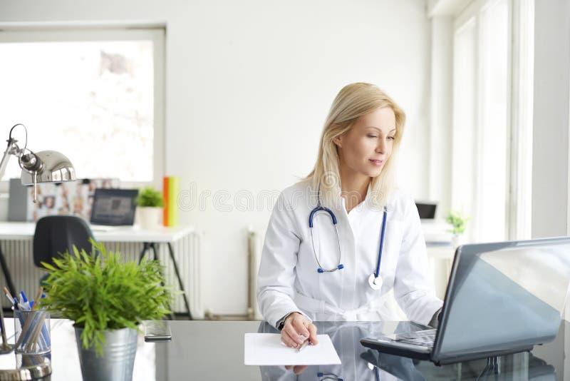 Säker kvinnlig doktor på kontorsskrivbordet arkivbilder