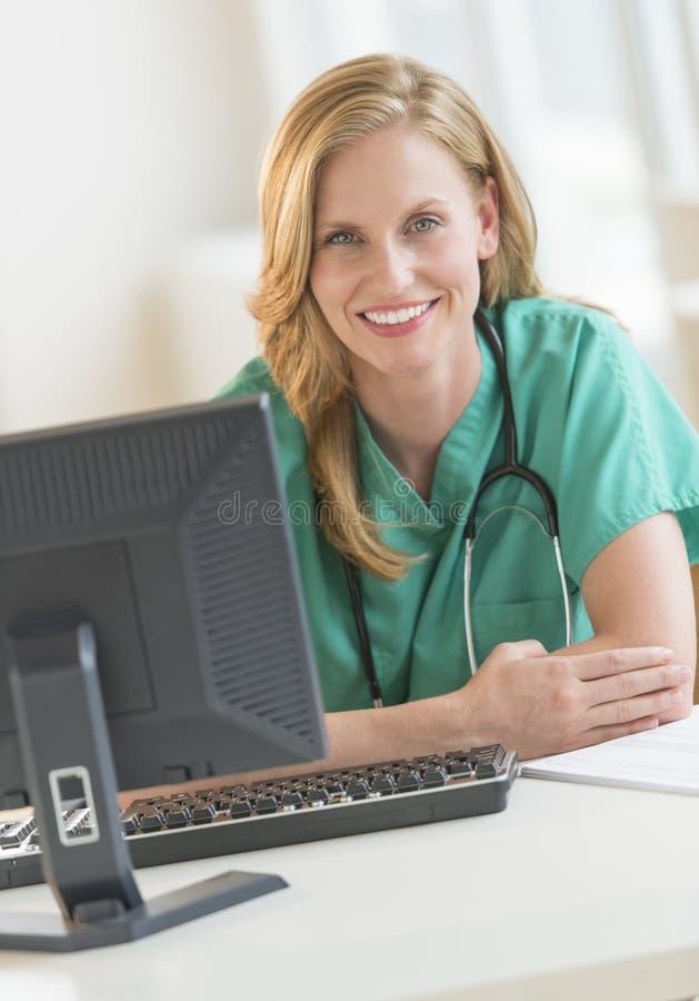 Säker kvinnlig doktor In Scrubs Leaning på sjukhusskrivbordet royaltyfria foton