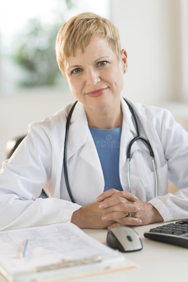 Säker kvinnlig doktor Sitting At Desk arkivbilder