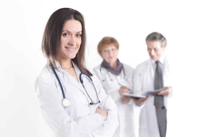 Säker kvinnlig doktorsterapeut på suddig bakgrund av kollegor royaltyfri fotografi