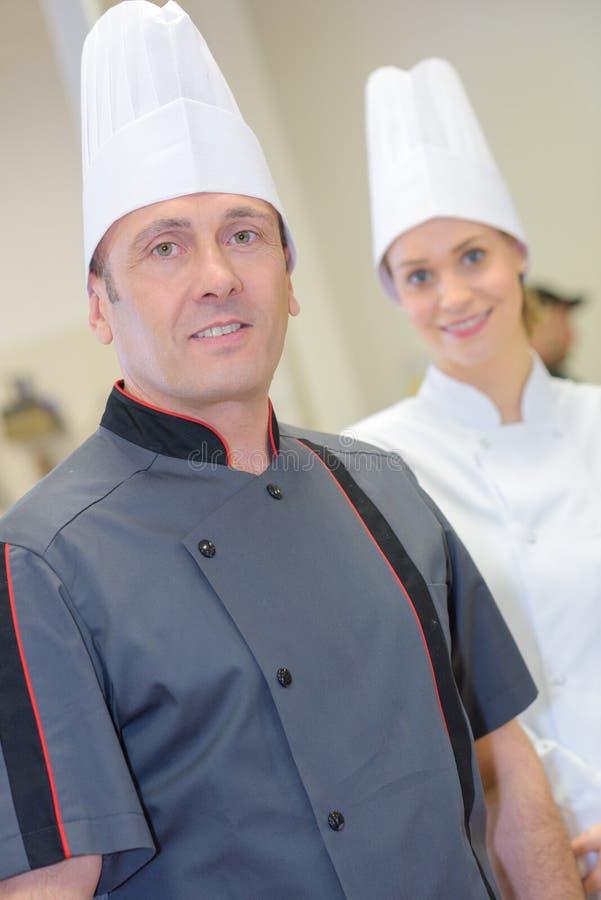 Säker kvinnlig för stående och mankock i kök royaltyfria bilder