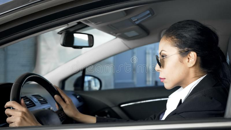 Säker kvinnlig i sammanträde för affärsdräkt i det tjänstgörande bilnationell säkerhetmedlet royaltyfri foto