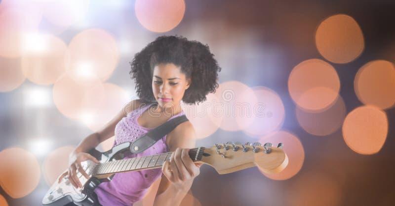 Säker kvinnlig musikkonstnär som spelar gitarren över bokeh royaltyfria bilder