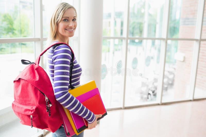 Säker kvinnlig student med ryggsäcken och böcker arkivbild