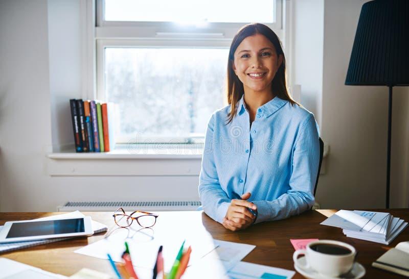 Säker le kvinna på skrivbordet fotografering för bildbyråer