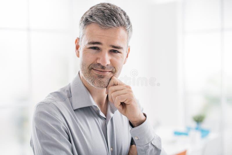 Säker le man som poserar i kontoret och ler på kameran arkivbild