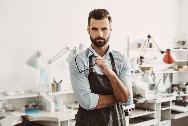 säker ledare Stående av det bärande förklädet för säker manlig juvelerare och rymmaexponeringsglas fotografering för bildbyråer