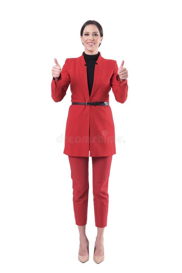 Säker lycklig affärskvinna i den eleganta röda dräkten som visar tummar upp gest och ler på kameran fotografering för bildbyråer
