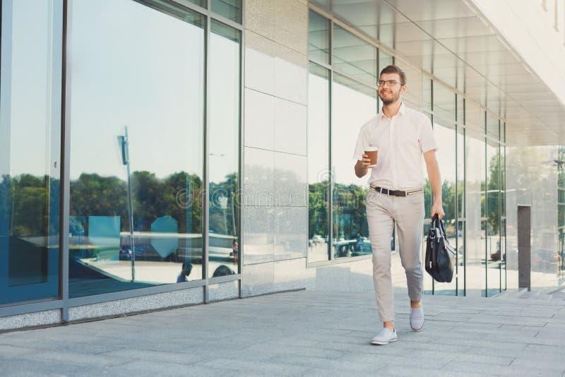Säker lycklig affärsman med kaffe som går, och en påse fotografering för bildbyråer
