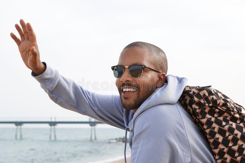 Säker lycklig ung afrikansk amerikanmanhipster i den hoody sporten och solglasögon som ser en vän på stranden arkivbild