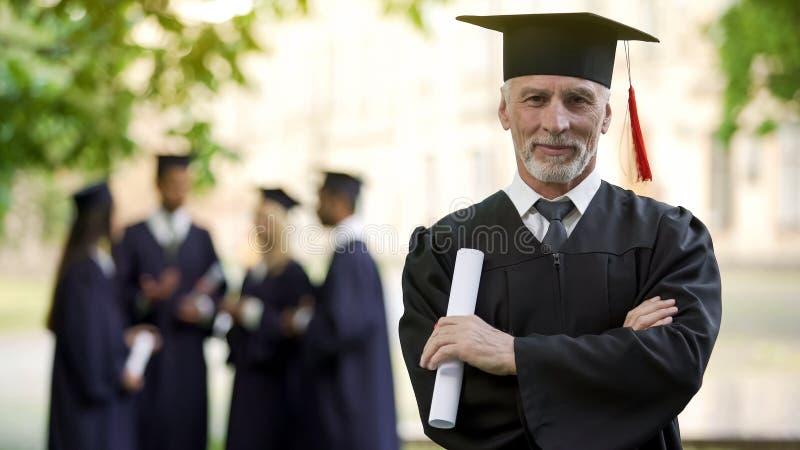 Säker man i avläggande av examendräkten, manlig erhållande grad, universitetskarriär fotografering för bildbyråer