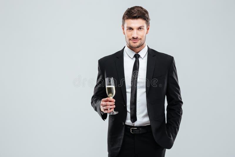Säker man i hållande exponeringsglas för dräkt och för band av champagne royaltyfria bilder