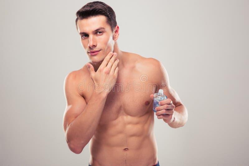 Säker man som applicerar ansikts- lotion arkivfoto