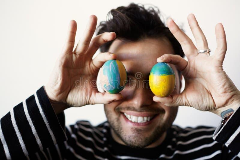 Säker man som rymmer den fega nya organiska äggframdelen av hans framsida på vit bakgrund close upp royaltyfri bild