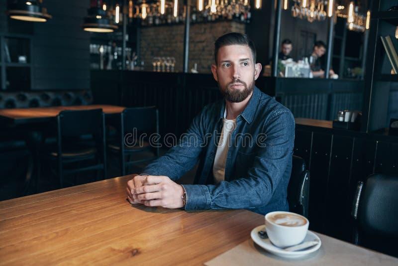 Säker man som tycker om en kopp kaffe, medan ha lunch för arbetsavbrott i inomhus kafét som ser eftertänksamt fotografering för bildbyråer
