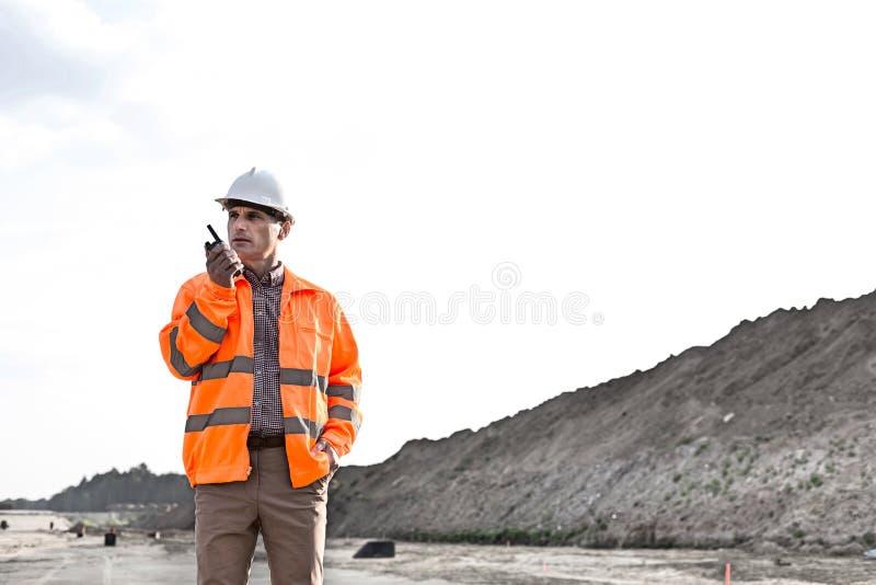 Säker manlig arbetsledare som använder walkie-talkie på konstruktionsplats mot klar himmel royaltyfri fotografi