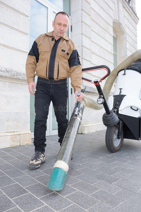 Säker manlig dörrvakt med dammsugare på gatan fotografering för bildbyråer