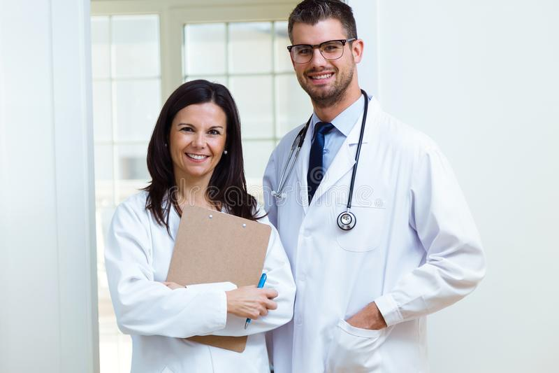 Säker manlig doktor och hans sjuksköterska som ser kameran i kontoret arkivfoto