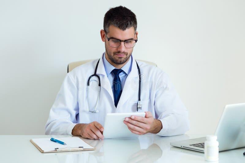 Säker manlig doktor som använder hans digitala minnestavla i kontoret arkivbilder