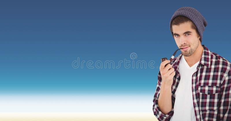 Säker manlig hipster som röker röret mot blå bakgrund arkivbild