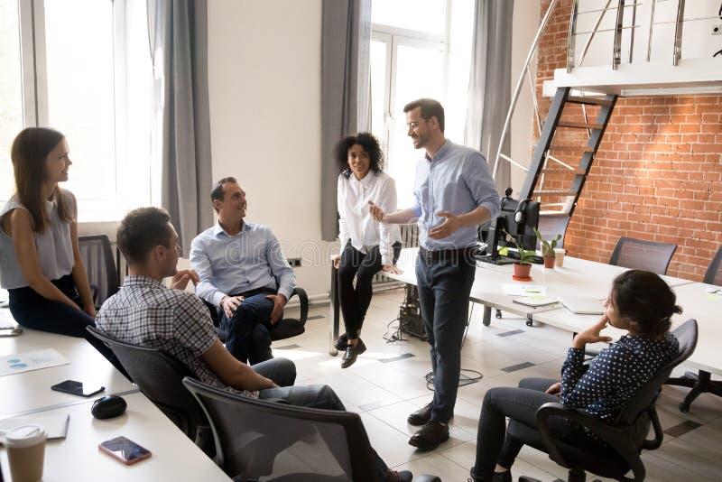 Säker manlig ledare, lagledare som talar med gruppen av kontorsarbetare royaltyfri bild