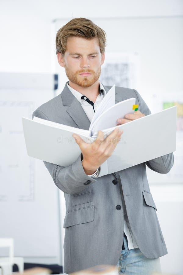 Säker manlig märkes- hållande mapp i idérikt kontor royaltyfria foton