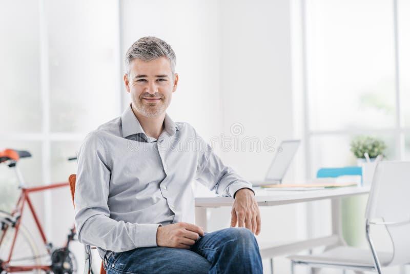 Säker modern affärsman som sitter i hans kontor och ler på kameran royaltyfri fotografi