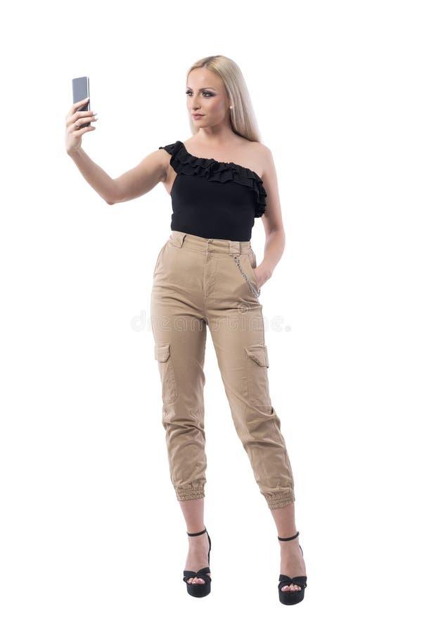 Säker modern för kvinnamode för blont hår som influencer för livsstil tar foto med den smarta telefonen arkivbilder