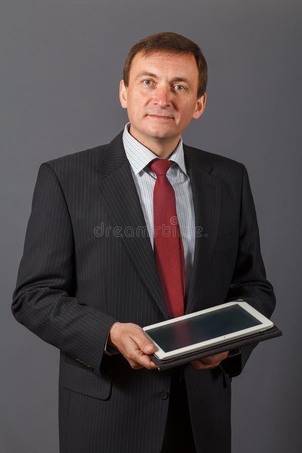 Säker mogen affärsman som framme står av en grå backgro arkivfoto