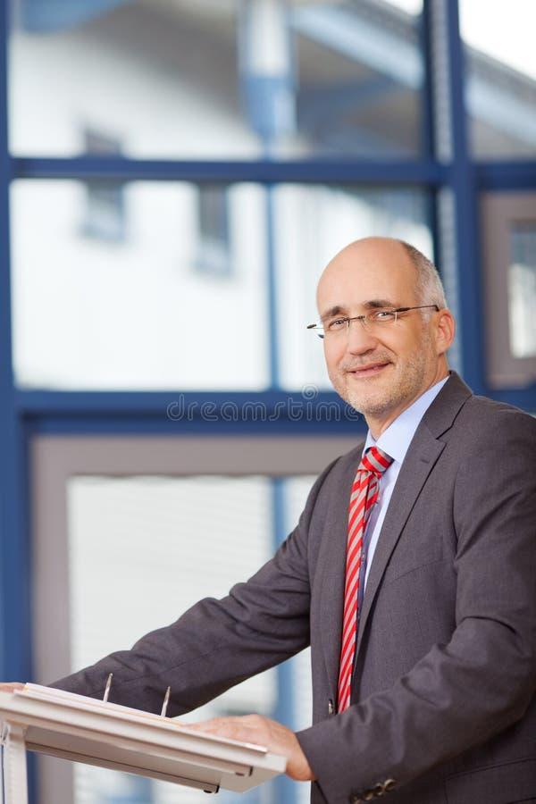 Säker mogen affärsman Standing In Office arkivbild