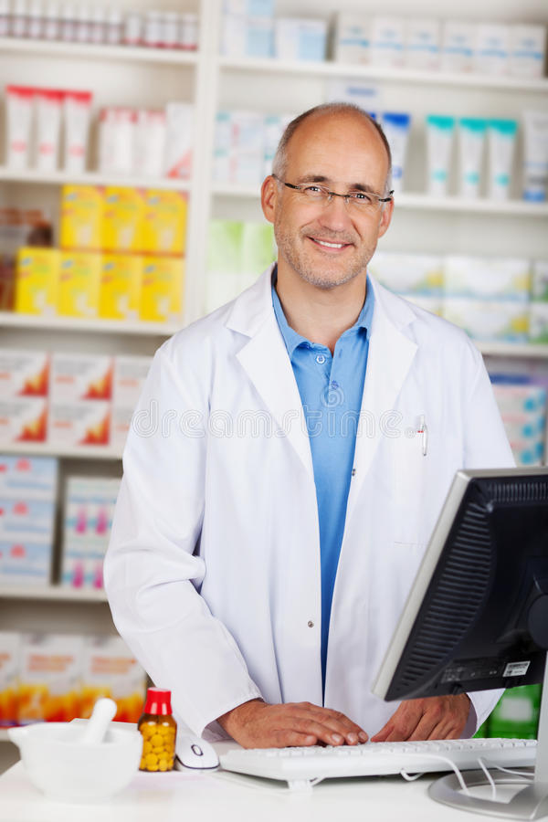 Säker mogen apotekare Standing At Counter arkivbild