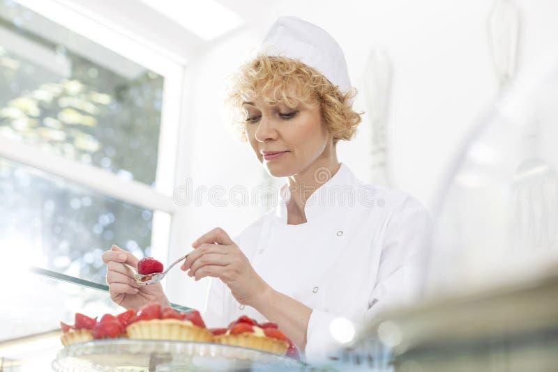 Säker mogen kock som ordnar nya jordgubbetarts i restaurang royaltyfri bild