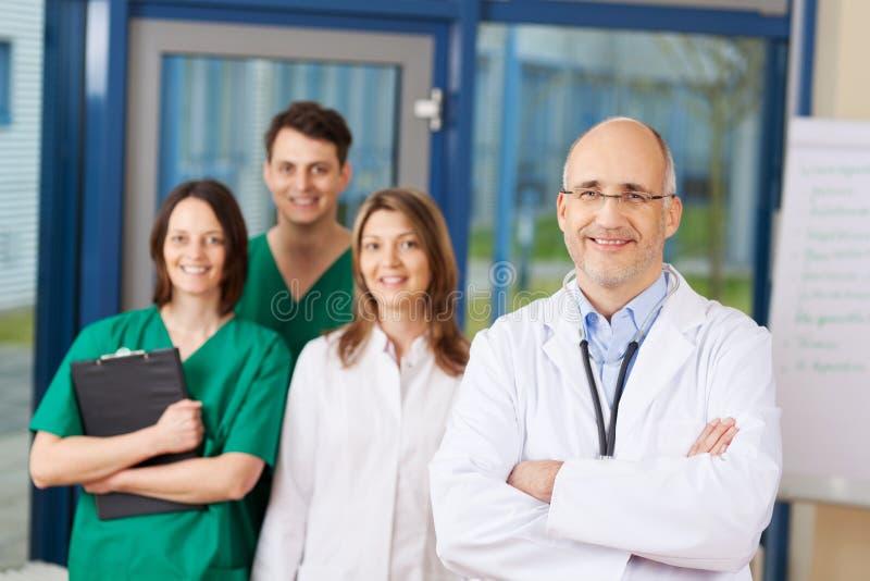Säker mogen manlig doktor With Team In Background royaltyfri foto