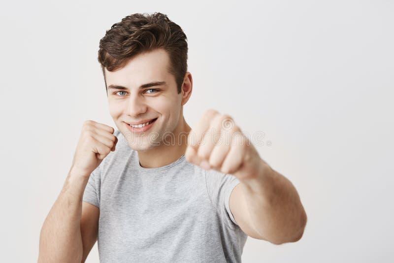 Säker muskulös caucasian idrottsman med nävar för iklädd grå skjorta för mörkt hår främsta hållande och att gå att slåss och royaltyfri foto