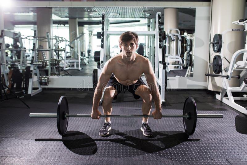 Säker muskulös manutbildning squats med skivstånger uppe i luften Closeupstående av den yrkesmässiga mangenomköraren med skivstån arkivbilder