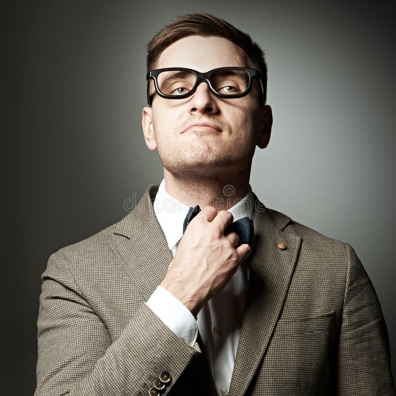 Säker nerd i glasögon som justerar hans fluga arkivfoto