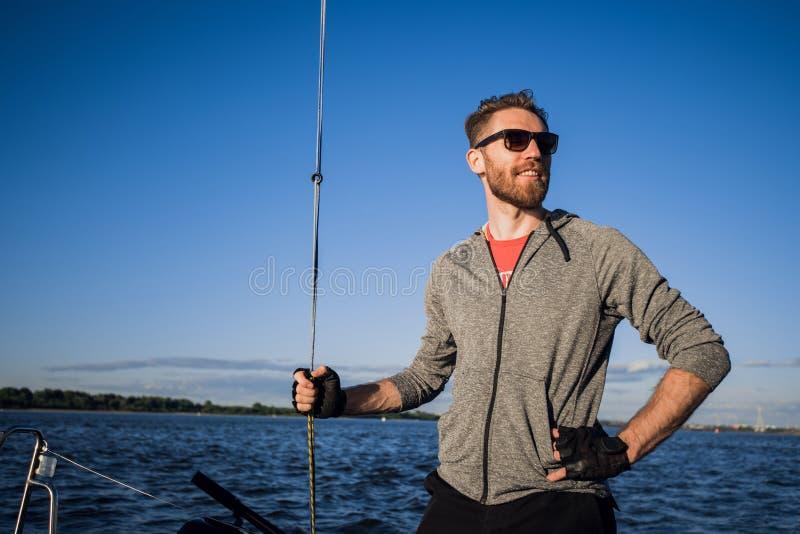 Säker och lycklig sjömanställning på yachten Han ser bort Grabben rymmer repet Han är klar för en tur Sun går besegrar royaltyfri foto
