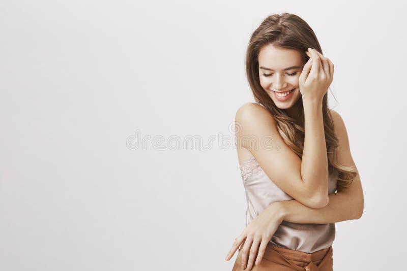 Säker och mjuk kvinnlig som rodnar från komplimang Stående av den near framsidan för flirty sinnligt kvinnligt hår för kvinna rör royaltyfri fotografi