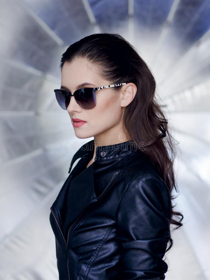 Säker och sexig brunett med den härliga framsidan, stilfull solglasögon, svartläderomslaget och den rebelliska frisyren royaltyfria foton