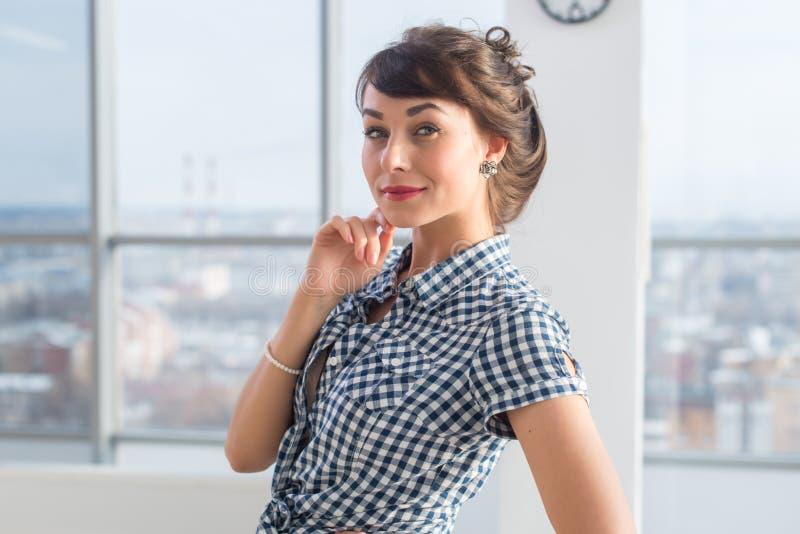 Säker positiv ung kvinna som poserar och att rymma handen bredvid framsidan som ler Ursnygg vänlig seende brunettflicka royaltyfri foto