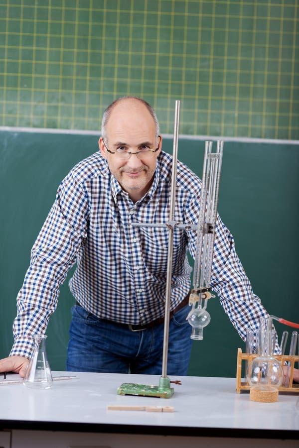 Säker professor Leaning On Desk i vetenskapsgrupp royaltyfri fotografi
