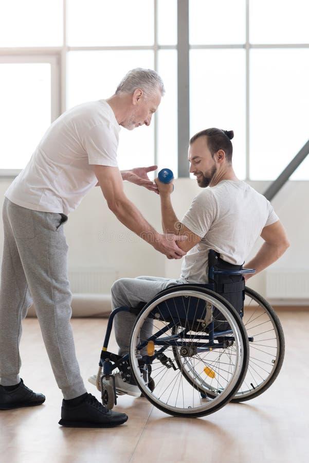 Säker rörelsehindrad man som övar med hans lagledare i idrottshallen arkivfoton