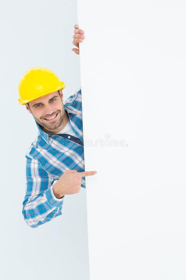 Säker repairman som pekar på den tomma affischtavlan arkivfoton