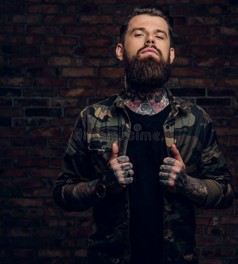 Säker skäggig grabb med tatueringar på hans händer och hals i den militära skjortan Studiofoto mot tegelstenväggen royaltyfri fotografi