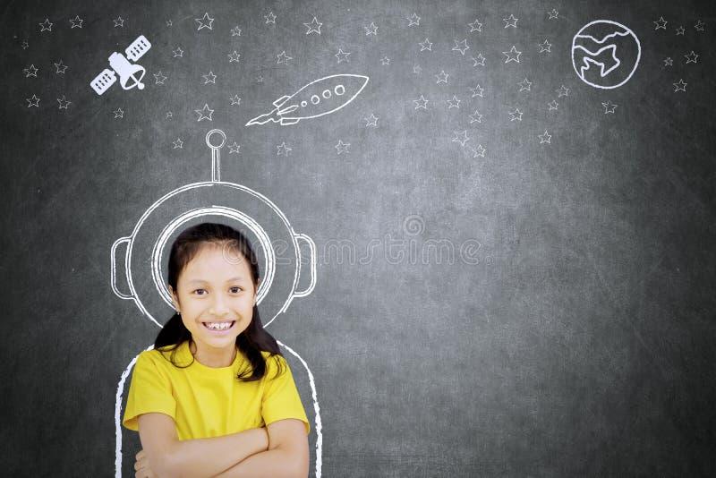 Säker skolflicka som föreställer vara en astronaut royaltyfria foton
