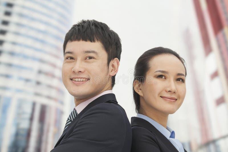Säker stående ung affärsman och affärskvinna tillbaka att dra tillbaka och att le royaltyfri foto