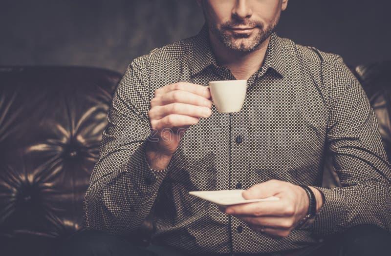 Säker stilig skäggig man med kopp kaffesammanträde på den bekväma lädersoffan på mörk bakgrund royaltyfri foto